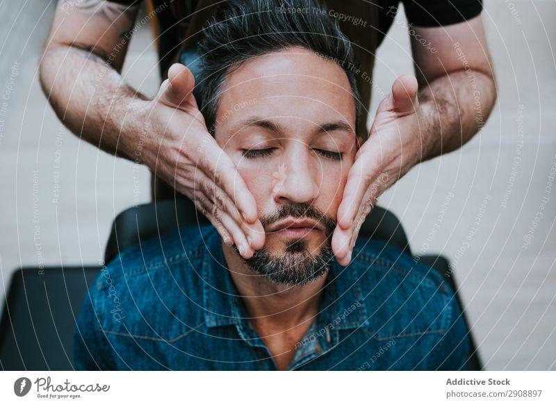 Barbier macht Gesichtsmassage bei einem gutaussehenden Mann. Massage Stil geschlossene Augen professionell sitzen Stuhl Behandlung Gesundheit Therapie