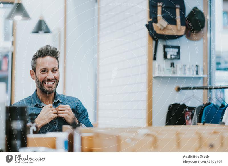 Mann schaut in den Spiegel und berührt den Bart im Salon. Vollbart Überprüfung Reflexion & Spiegelung gutaussehend Stil professionell berühren Blick Mode