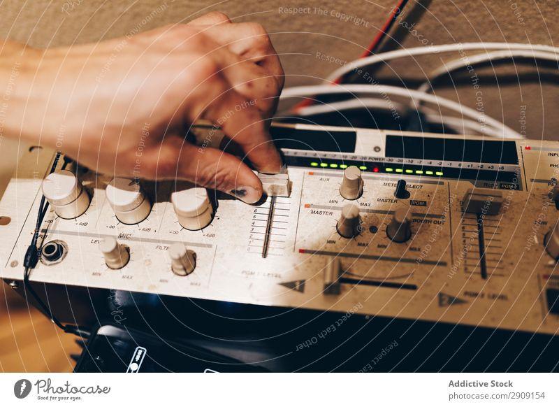Anonymer männlicher Musiker, der einen Verstärker abstimmt. Mann Hand Spielen Synthesizer Studioaufnahme professionell Jugendliche Gerät Rhythmus Klang Takt