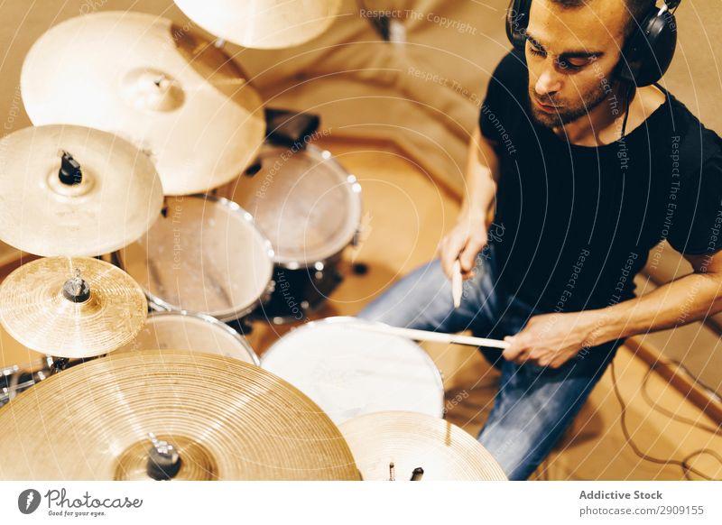 Mann mit Kopfhörern spielt am Schlagzeug Trommel Spielen positiv Studioaufnahme Musik