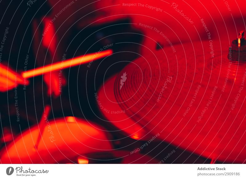 Anonymer Mann mit Trommelstöcken, die auf Trommeln in Rötung spielen. Trommelschlegel Hand Röte rot Licht Spielen Studioaufnahme Musik professionell Jugendliche