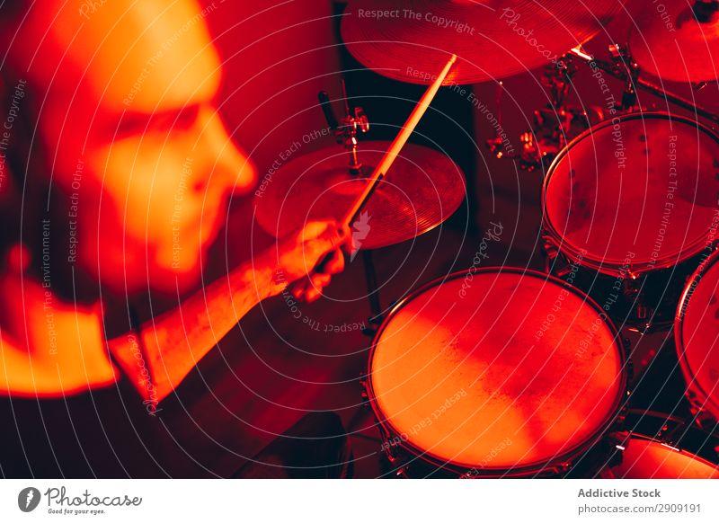 Mann mit Trommelstöcken, die auf Trommeln in Rötung spielen. Trommelschlegel Röte Spielen Studioaufnahme Musik professionell Jugendliche Schlagzeuger Gerät