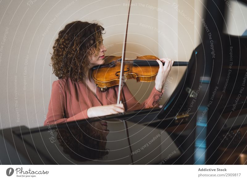 Frau, die neben einem Klavier sitzt und eine Geige spielt. herumfuchteln Spielen Musik Geiger Orchester Instrument Klassik Musiker Hand Musical Mensch Schnur