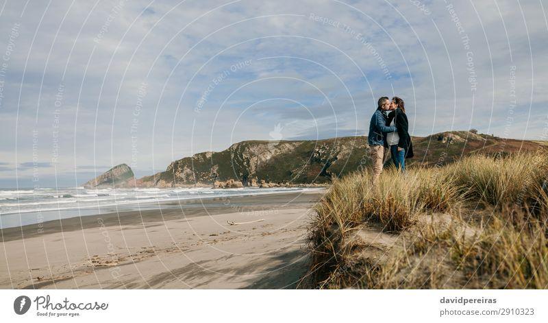 Ein Paar küsst sich am Strand. Lifestyle ruhig Freizeit & Hobby Meer Wellen Winter Frau Erwachsene Mann Eltern Familie & Verwandtschaft Natur Landschaft Sand