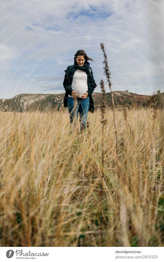 Schwangere Frau sieht ihren Bauch an. Lifestyle Freude Glück schön Freizeit & Hobby Mensch Baby Erwachsene Mutter Familie & Verwandtschaft Natur Landschaft Gras