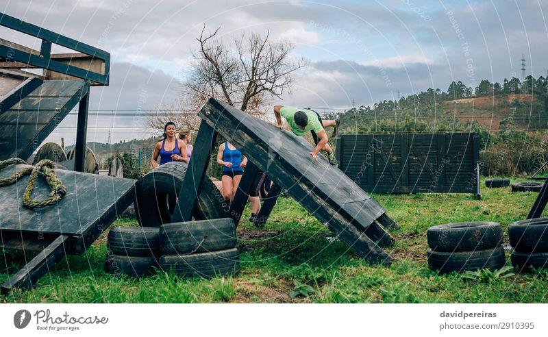 Teilnehmer des Hindernisparcours Kletterwand Lifestyle Sport Klettern Bergsteigen Mensch Frau Erwachsene Mann Menschengruppe Wiese springen authentisch stark