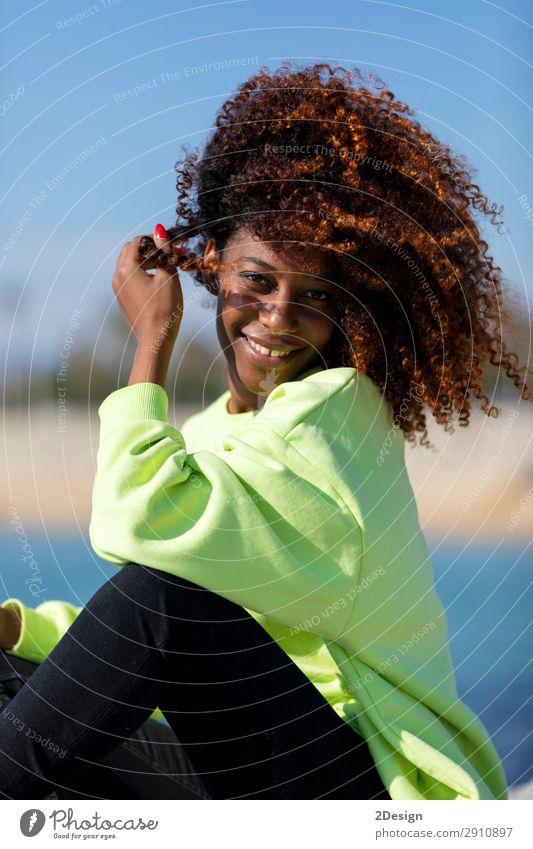 Seitenansicht einer schönen lockigen Afrofrau, die auf dem Wellenbrecher sitzt. Lifestyle Stil Haare & Frisuren Gesicht Meer Mensch feminin Junge Frau