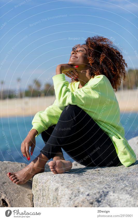 Seitenansicht der schönen lockigen Afrofrau, die auf dem Wellenbrecher sitzt. Lifestyle Stil Haare & Frisuren Gesicht Meer Mensch feminin Junge Frau Jugendliche