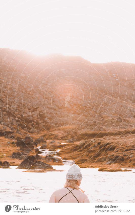 Frau in der Nähe von Wasser und Hügel am Ufer an sonnigen Tagen Küste Schönes Wetter Oberfläche Himmel Sonne Höhe Hut kalt Jugendliche Natur Berge u. Gebirge