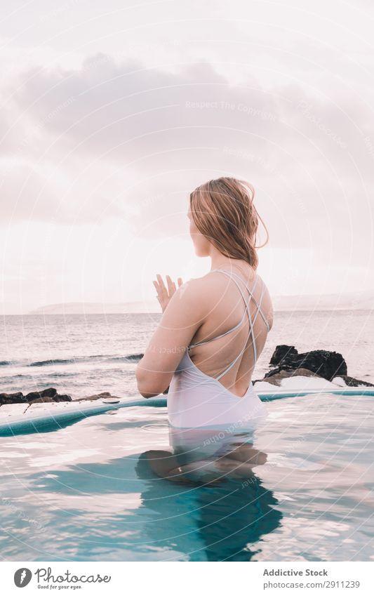 Frau sitzt im Pool in der Nähe von Steinen. Schwimmbad Jugendliche aussruhen Wasser geschlossene Augen Felsen Himmel Wolken Sommer Körper Erholung Gesundheit