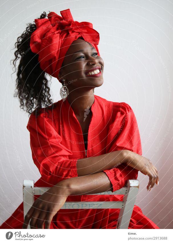 Apolline Stuhl feminin Frau Erwachsene 1 Mensch Kleid Schmuck Kopftuch brünett langhaarig Locken Erholung lachen sitzen authentisch außergewöhnlich