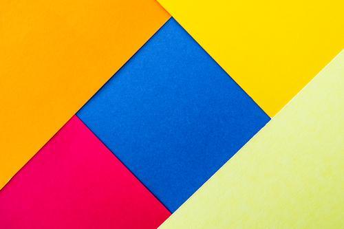 grafisches Hintergrundbild aus Buntpapier blau Farbe rot gelb Textfreiraum orange rosa leuchten Papier einfach Neigung graphisch Quadrat Basteln Geometrie