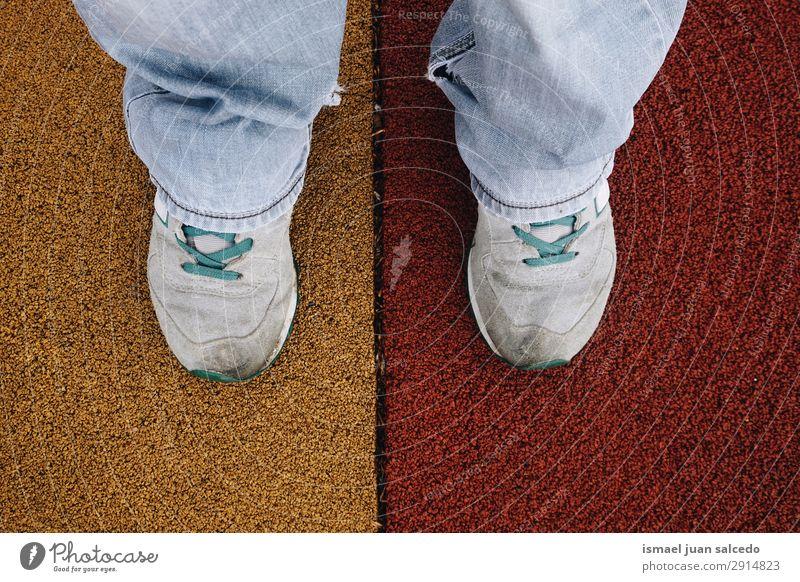 Füße auf dem bunten Boden des Spielplatzes Fuß Körperteil Mensch Beine Turnschuh Schuhe Sport Muskelshirt Lifestyle stehen mehrfarbig Straße Außenaufnahme