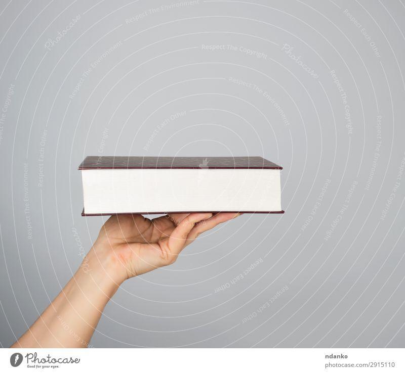 Hand hält ein geschlossenes Buch im Hardcover. lesen Mensch Frau Erwachsene Mann Arme Papier braun grau weiß Hintergrund blanko zugeklappt Entwurf Deckung