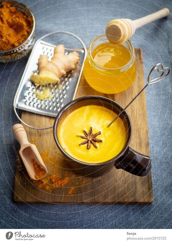 Goldene Milch mit Honig und Ingwer Lebensmittel Milcherzeugnisse Kräuter & Gewürze Curcuma Sternanis Ernährung Getränk Heißgetränk Tasse Schneidebrett Reibe