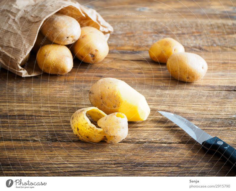 Kartoffeln in einer Papiertüte Lebensmittel Gemüse Ernährung Bioprodukte Vegetarische Ernährung Messer Gesunde Ernährung Brauner Holztisch gut lecker genießen