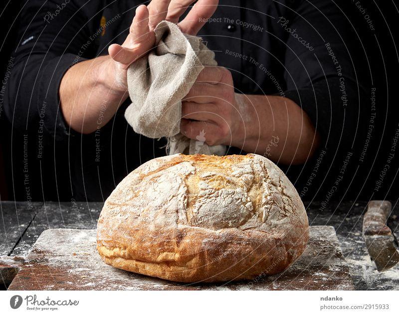 gebackenes Rundbrot auf einem Brett Teigwaren Backwaren Brot Ernährung Messer Tisch Küche Koch Mensch Hand Holz machen dunkel frisch braun schwarz Tradition
