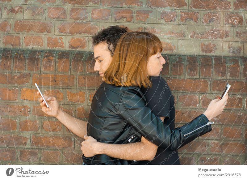 Ein junges Paar, das sich umarmt, während jeder auf sein eigenes Smartphone starrt. Lifestyle Glück schön Telefon PDA Technik & Technologie Internet Mensch Frau