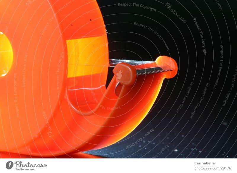 Kleberolle I Klebeband Langzeitbelichtung orange Schreibwaren Bürogerät Makroaufnahme Detailaufnahme Innenaufnahme Kunststoff Vor dunklem Hintergrund