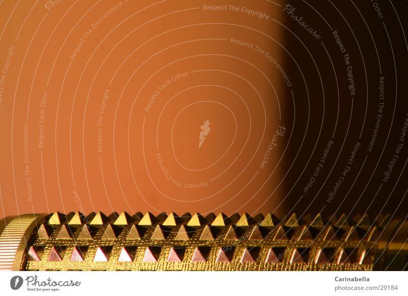 Massagerolle II Massagebürste glänzend obskur Massagestab Alluminium Pyramide Zacken Metall Kunstlicht Orange