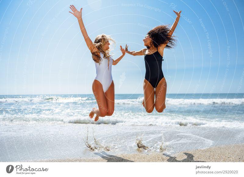 Zwei lustige Mädchen im Badeanzug springen an einem tropischen Strand im Sommer. Lifestyle Freude Glück schön Körper Haare & Frisuren Freizeit & Hobby
