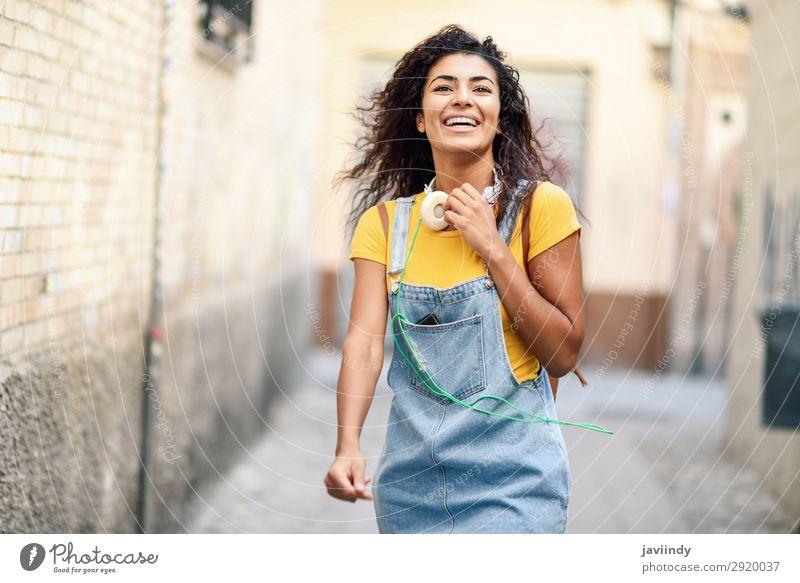 Junge afrikanische Frau mit Kopfhörern, die ins Freie geht. Lifestyle Stil Freude Glück schön Haare & Frisuren Mensch feminin Junge Frau Jugendliche Erwachsene