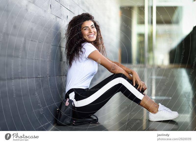 Fröhliche arabische Frau, schwarze lockige Frisur, die auf dem städtischen Boden sitzt. Lifestyle Stil Glück schön Haare & Frisuren Gesicht Sport Mensch feminin