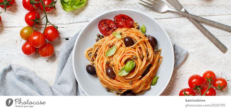 Spaghetti mit Tomatensoße, Oliven und Kapern Gemüse Mittagessen Abendessen Vegetarische Ernährung Teller Gabel Löffel Holz oben grün rot Tradition Spätzle