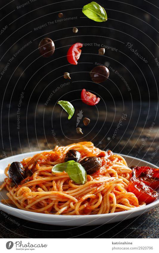 Spaghetti mit Tomatensoße, Oliven und Kapern Gemüse Mittagessen Abendessen Vegetarische Ernährung Teller Holz grün rot Tradition Spätzle puttanesca Kapriolen