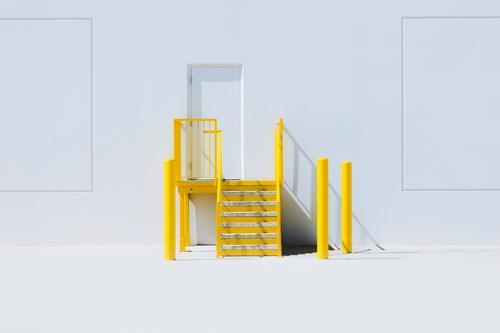 Yellow staircase with an entrance door and a white wall Design Amerika Industrieanlage Mauer Wand Fröhlichkeit frisch gelb stairs steps Hintergrundbild safety