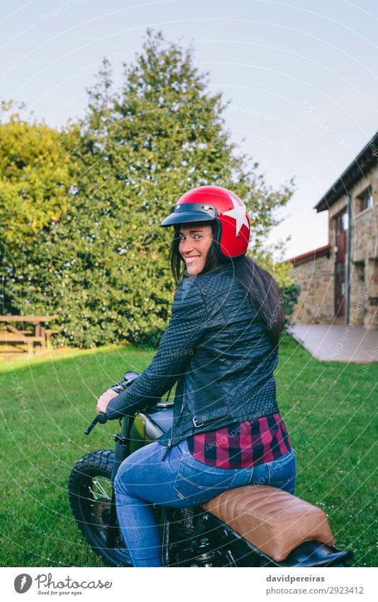 Frau mit Helm auf einem Custom-Motorrad Lifestyle Glück schön Haus Mensch Erwachsene Baum Gras Verkehr Fahrzeug Mode Jeanshose Lächeln authentisch retro