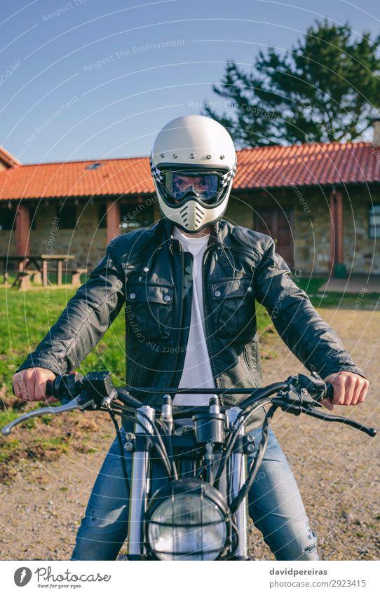 Mann mit Helm auf einem Custom-Motorrad Lifestyle Haus Mensch Erwachsene Baum Gras Verkehr Wege & Pfade Fahrzeug Mode Jeanshose authentisch retro Sicherheit