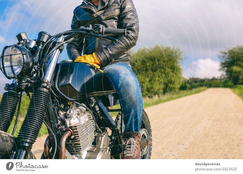 Mann auf einem Custom-Motorrad Lifestyle Mensch Erwachsene Natur Baum Verkehr Straße Wege & Pfade Fahrzeug Mode Jeanshose Handschuhe Stiefel warten authentisch