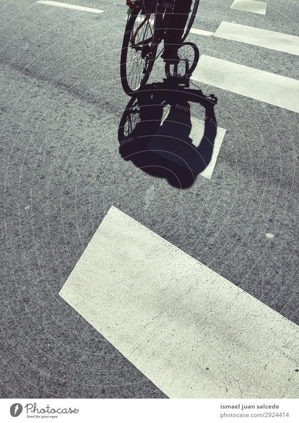 Mann auf dem Fahrrad Schatten Silhouette auf der Straße Sonnenlicht Boden Asphalt Hintergrund abstrakt Verkehr Fahrradfahren Zyklus Autositz Wagenräder