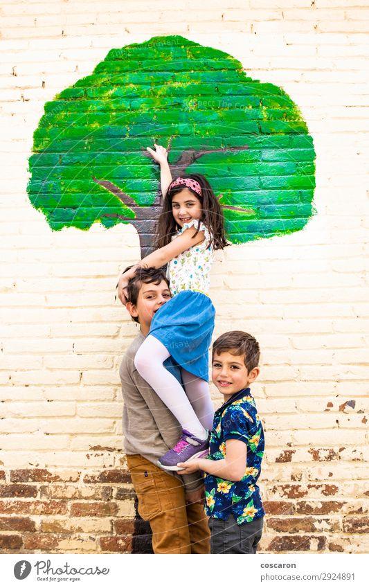 Drei Kinder spielen mit einem Baum, der an einer Wand gemalt ist. Lifestyle Freude Glück schön Leben Freizeit & Hobby Spielen Kinderspiel