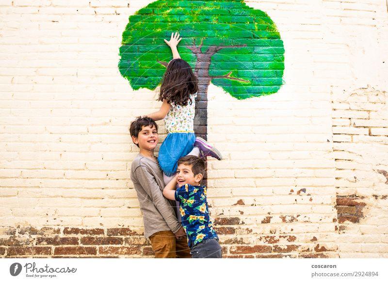 Drei Kinder spielen mit einem Baum, der an einer Wand gemalt ist. Lifestyle Freude Glück schön Freizeit & Hobby Spielen Ferien & Urlaub & Reisen Freiheit Sommer