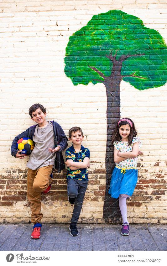 Porträt von drei Kindern mit gemaltem Baumhintergrund Lifestyle Freude Glück schön Freizeit & Hobby Spielen Sommer Sport Fußball Ball Schule Schulhof Mensch