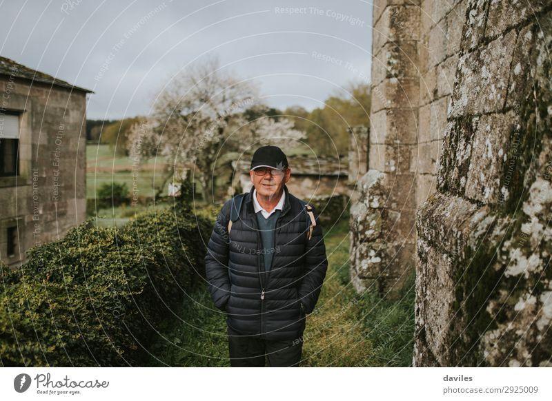 Ein Mann, der in einem ländlichen Dorf spazieren geht. Lifestyle Freude Erholung Freizeit & Hobby Ferien & Urlaub & Reisen Abenteuer wandern Ruhestand Mensch