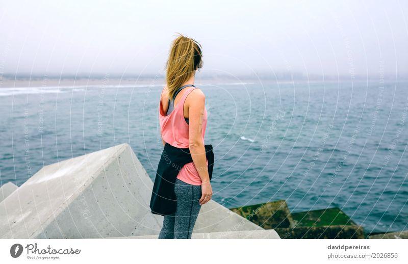 Nicht erkennbare junge Frau, die das Meer beobachtet. Lifestyle Wellness Erholung ruhig Sport Mensch Erwachsene Nebel Beton beobachten Fitness sportlich