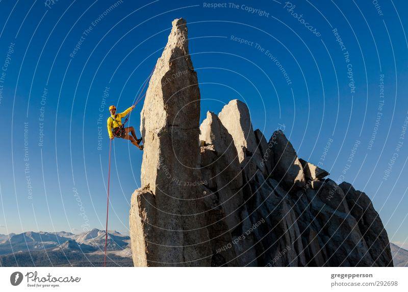 Kletterer beim Abseilen. Erholung Abenteuer Klettern Bergsteigen Seil Mann Erwachsene 1 Mensch 30-45 Jahre Felsen Gipfel Helm selbstbewußt Mut Vertrauen