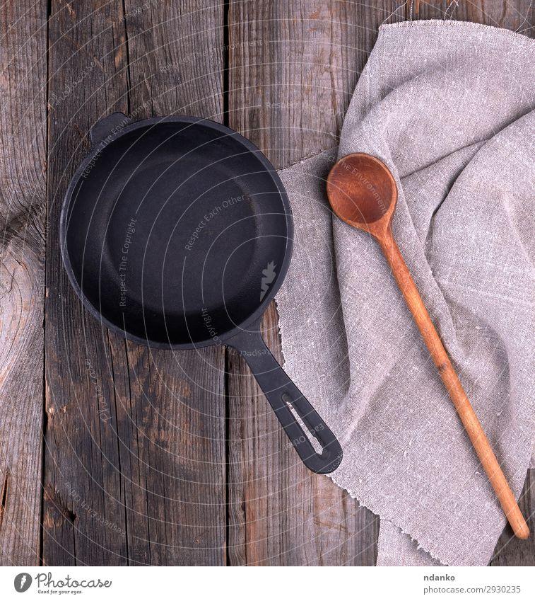 leere schwarze runde Bratpfanne mit Griff Pfanne Löffel Tisch Küche Holz Metall alt oben Sauberkeit braun grau Hintergrund Holzplatte gießen Essen zubereiten