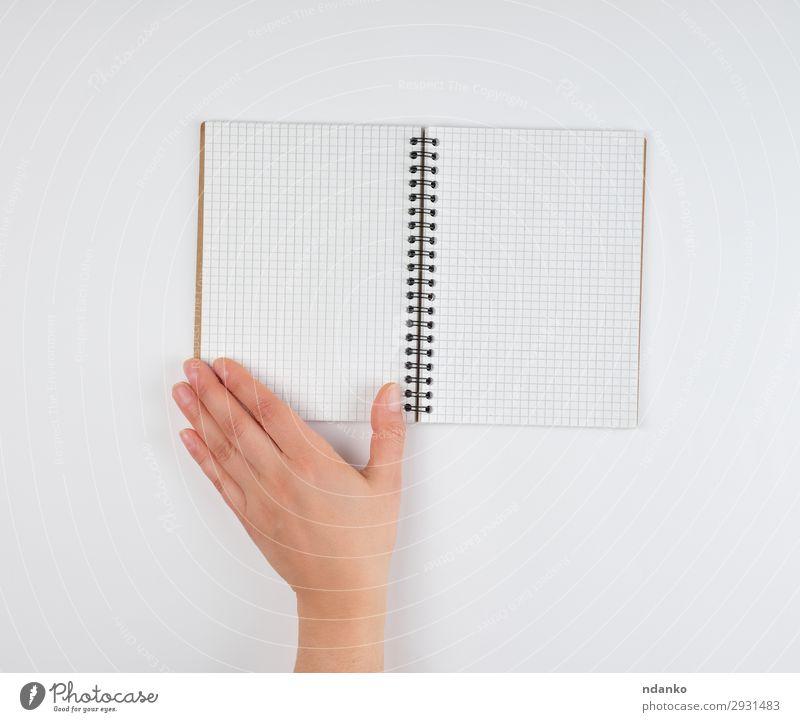 leeres offenes Notizbuch in einer Zelle und einer weiblichen Hand Schule lernen Büro Business Mensch Frau Erwachsene Arme Finger Buch Papier schreiben weiß