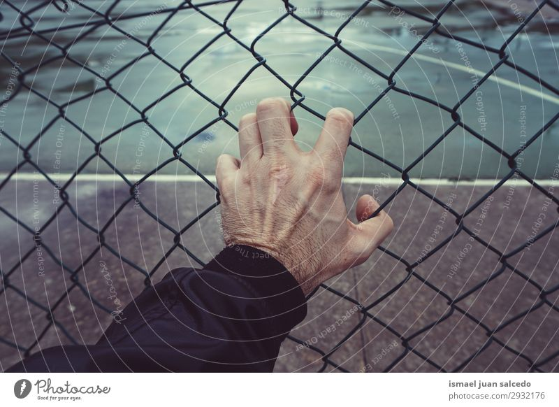 von Hand einen metallischen Zaun auf der Straße greifen. Mann Mensch Finger Körper Arme Metall Außenaufnahme packend