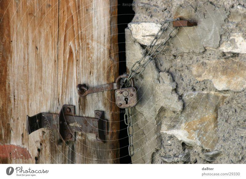 Altes Türschloß Türschloss Riegel Vorhängeschloss Mauer Wand Holztür Steinwand Burg oder Schloss Kette alt