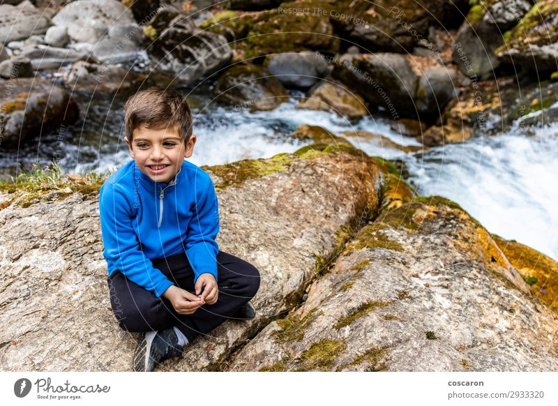 Süßer kleiner Junge sitzt in der Nähe eines wilden Flusses. Lifestyle Stil Freude Glück schön Freizeit & Hobby Ferien & Urlaub & Reisen Expedition Sommer