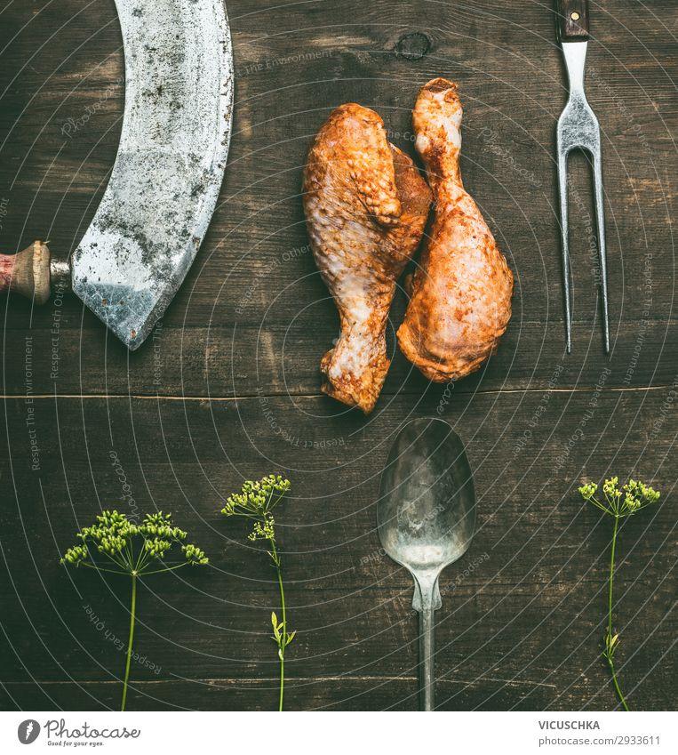 Rohe, vom Grill marinierte Hühnerkeule mit frischen Kräutern und Küchenutensilien auf rustikalem Holzgrund, Draufsicht. Vorbereitung des Grills roh Barbecue