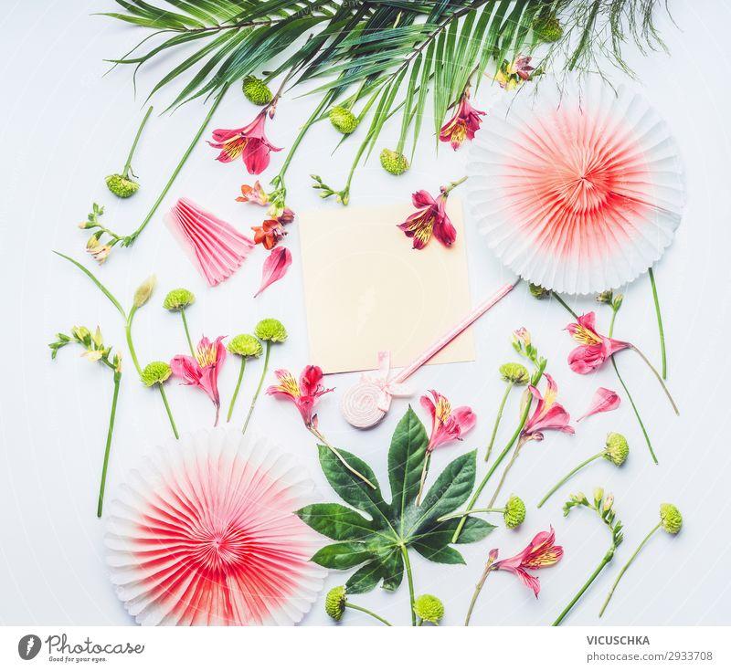 Leere Grußkarte mit Papier-Partyfächern, tropischen Blättern und exotischen Blumen auf weißem Hintergrund, Ansicht von oben. Flacher Schlag. Rahmen. Kopierraum für Ihren Text oder Ihr Design
