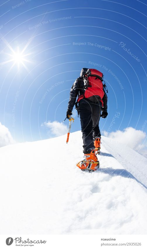 Ein Bergsteiger erreicht den Gipfel eines verschneiten Berges Freude Ferien & Urlaub & Reisen Abenteuer Freiheit Expedition Winter Schnee Berge u. Gebirge Sport