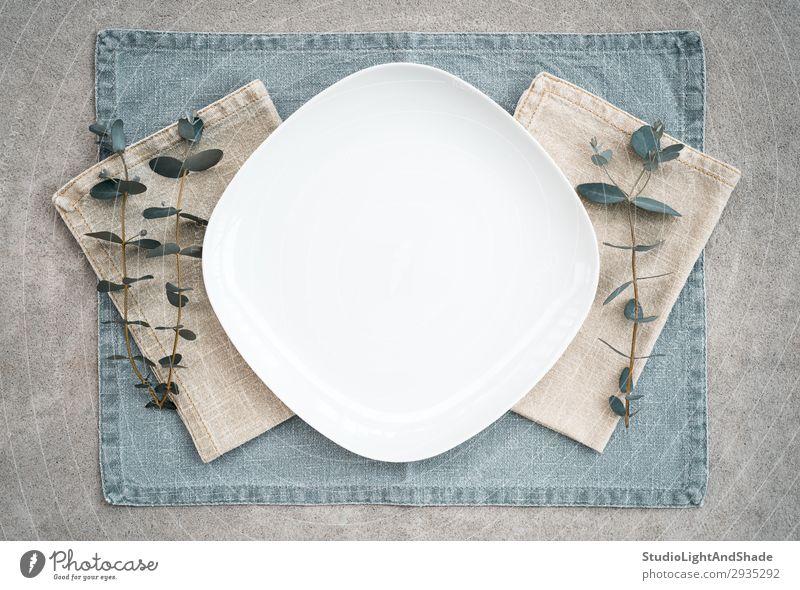 Elegante Tischdekoration mit Eukalyptuszweigen verziert Abendessen Teller elegant Stil Design Innenarchitektur Küche Restaurant Pflanze Blatt Stoff Stein Beton