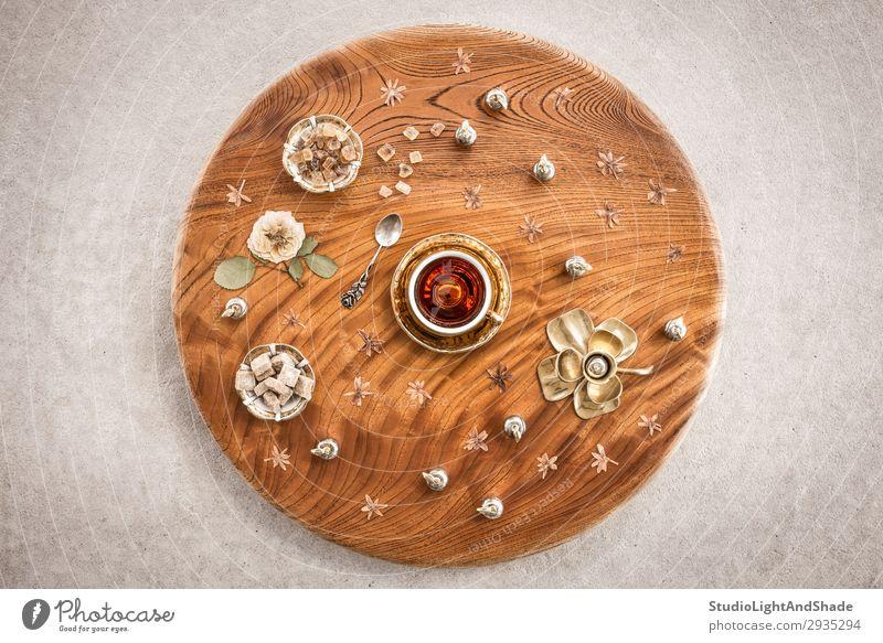 Runder Holztisch mit Tee und Blumen Dessert Süßwaren Getränk Teller Löffel Design Tisch Blatt Beton Metall natürlich retro braun gold Farbe rund Teetrinken